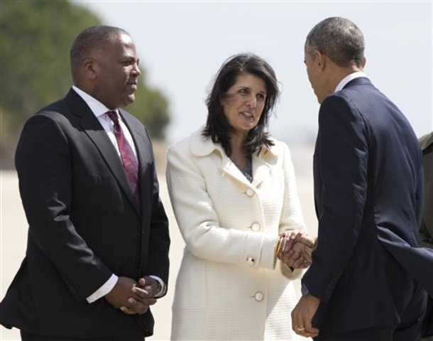 South Carolina Gov. Nikki Haley, center, accompanied by Columbia, S.C., Mayor Stephen Benjamin, greets President Barack Obama upon his arrival on Air Force One at Columbia Metropolitan Airport, Friday, March 6, 2015, in Columbia, S.C., en route to Benedict College in Columbia, S.C., for a town-hall meeting about the importance of community involvement. (AP Photo/Carolyn Kaster)